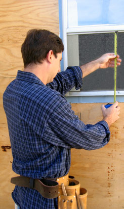 picture of a man measuring his New Jersey home for a home maintenance project