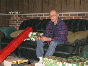 an elderly man showing his Christmas presents