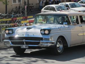 Men drive vintage American cars