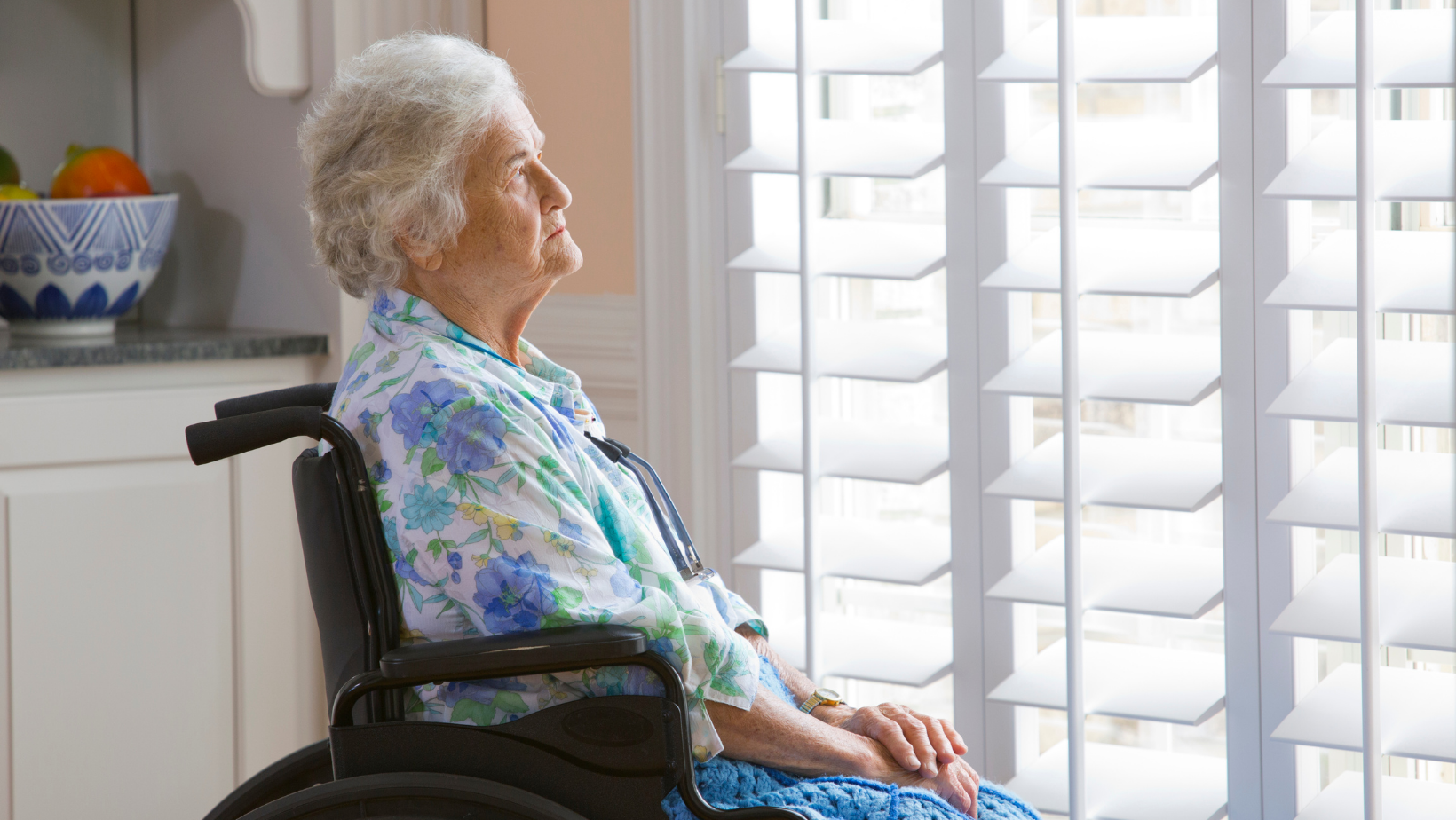 an older woman in a wheelchair, sitting in her kitchen, looking out the window