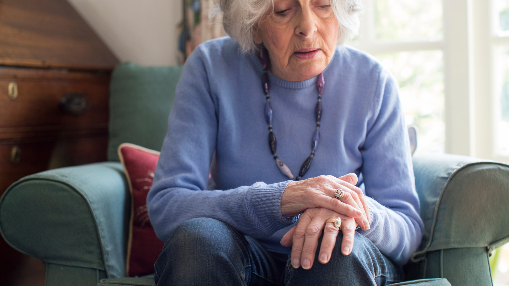 a older woman with Parkinson's, sitting in a chair, hunched over